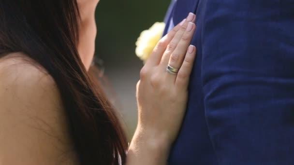 Ženich a nevěsta navzájem obejmout v sunny park