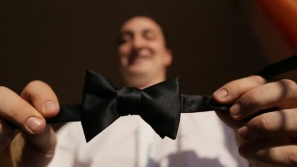 Groom showing his tie on the camera.