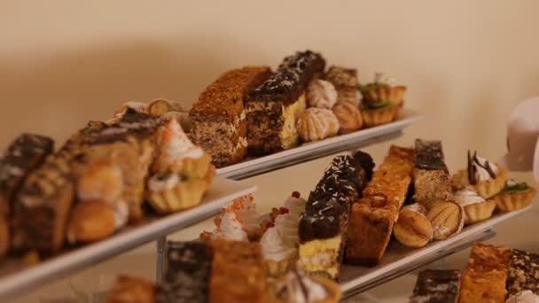 Stůl s mnoha cukrovinky, sušenky a koláče. Svatební dezert.