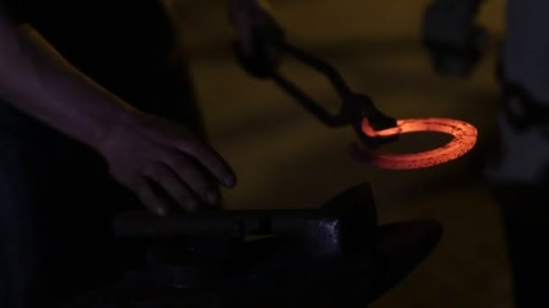 The smith in a smithy forges a horseshoe