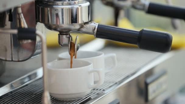 A shiny silver espresso machine makes coffee