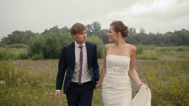 Nevěsta a ženich na poli s deštěm