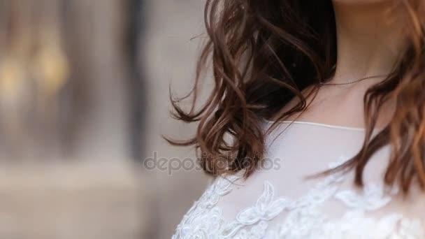 Boldog, fiatal lány, egy esküvői ruha, ugrás, és a háttérben a régi várfalak mozgó