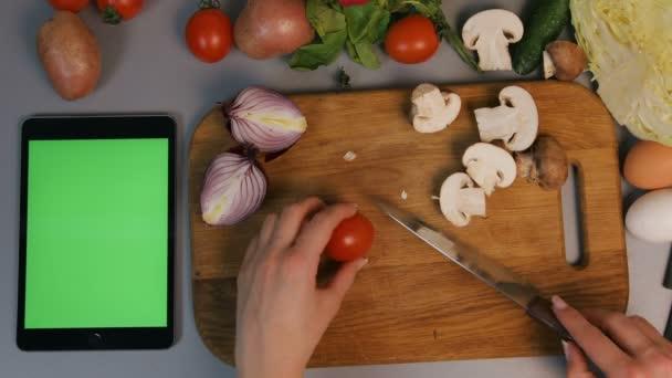 Nő vágás vegatables vágódeszka, a konyhában a.