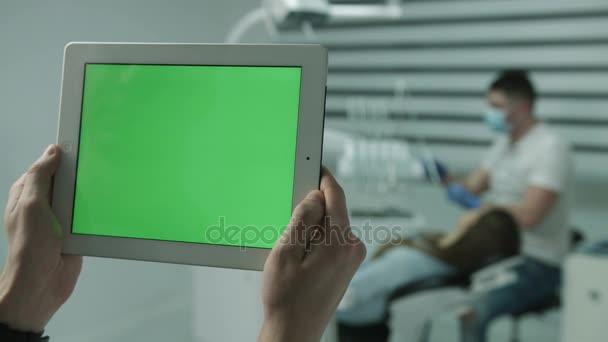 Počítače tablet pc, na pozadí pracovní mužské zubař a ležící pacientka