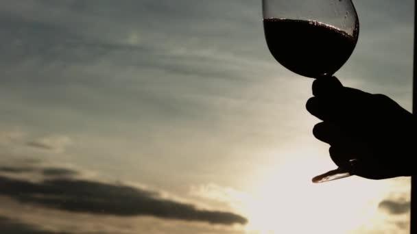 Ruka se skla naplněné červeným vínem