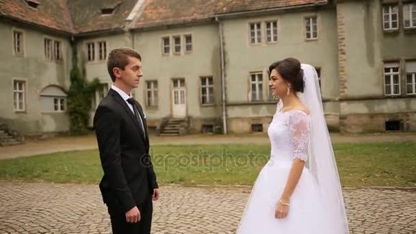 Krásná nevěsta chůzi na ženicha, objímání a líbání ho poblíž hradu