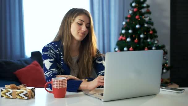 Mladá dívka SMS vánoční přání s její přenosný počítač. Novoroční večírek