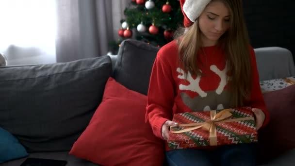 S úsměvem mladá žena se snaží najít co v dar, ještě pole na pozadí vánoční stromeček