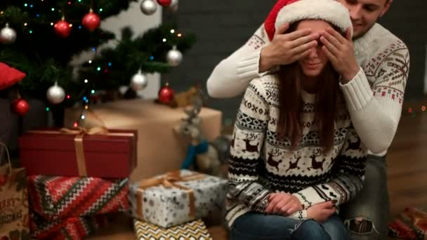 Mladý muž, překvapivé, atraktivní žena a dávat vánoční dárek na Vánoce strom pozadí s dárky. Detailní záběr.