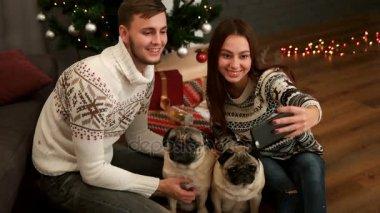 Boldog fiatal pár a szerelem mosolyogva, és így selfie pár mopszli kutya a karácsonyfa közelében. Szemközti nézet