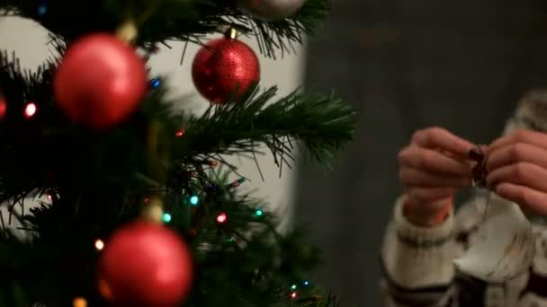 Mladá žena ruce, zdobí vánoční stromeček červené a stříbrné hračky v barevný svetr. Detailní záběr.