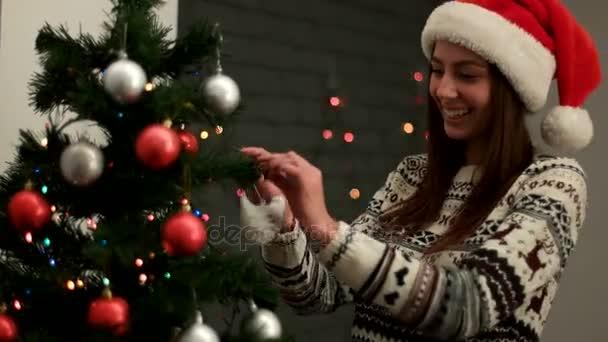 2315f89bfd694 Молодая женщина счастлива в шапке Санта-Клауса улыбаясь и украшения Рождественская  елка красный и серебристый игрушки. Крупным планом– стоковое видео
