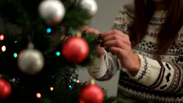Mladá žena ruce, zdobí vánoční stromeček červené a stříbrné hračky v obývacím pokoji. Detailní záběr