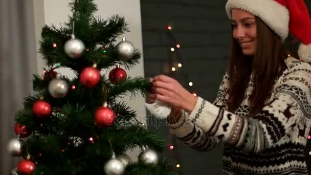 Santa claus kalap mosolyogva és díszítő a karácsonyfa ezüst játékok-ra könnyű háttér mellett vonzó boldog nő. Közelről.