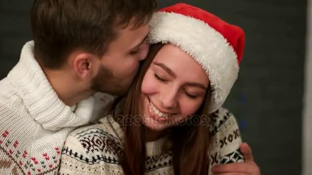 Aranyos fiatal szerelmespár huging, és élvezi időt együtt. Attracive ember átölelve nő a santa claus kalap-nappali.