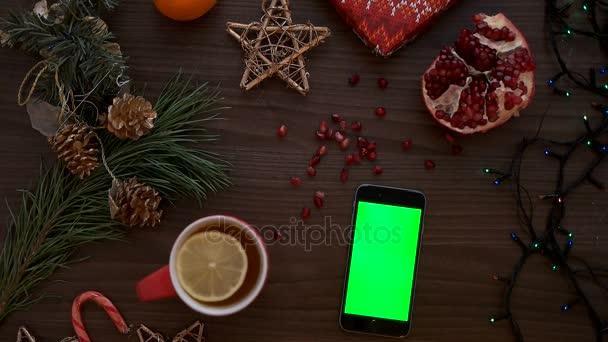 Pohled shora muž ručně pomocí chytrého telefonu s zeleným plátnem. Prst posouvání stránky dolů na dotykovém displeji. Vánoční podrobnosti o dřevěný stůl pozadí. Chroma klíč