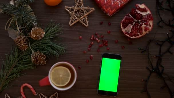 Pohled shora muž ručně pomocí chytrého telefonu s zeleným plátnem. Posouvání stránky prst na dotykovém displeji. Vánoční podrobnosti o dřevěný stůl pozadí. Chroma klíč