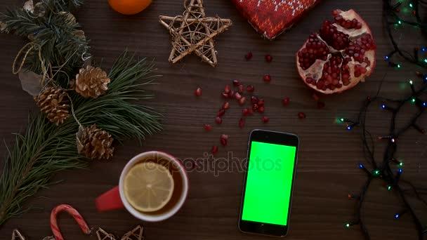 Pohled shora muž ručně pomocí chytrého telefonu s zeleným plátnem. Prst na dotykovém displeji. Vánoční podrobnosti o dřevěný stůl pozadí. Chroma klíč