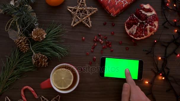 Vánoční pohled shora. Člověk ruku pomocí chytrého telefonu s zeleným plátnem. Prst posouvání stránky dolů na dotykovém displeji. Krásné vánoční podrobnosti o dřevěný stůl pozadí. Chromatický klíč. Pohled shora