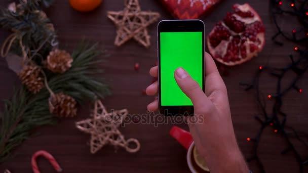 Vánoční pohled shora. Člověk ruku pomocí chytrého telefonu s zeleným plátnem. Posouvání stránky prst na dotykovém displeji. Vánoční podrobnosti o dřevěný stůl pozadí. Chromatický klíč. Pohled shora
