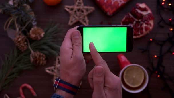 Vánoční pohled shora. Muž držel chytrý telefon s zeleným plátnem. Vodorovně. Posouvání stránky prst na dotykovém displeji. Vánoční podrobnosti o dřevěný stůl pozadí. Chromatický klíč. Nad zobrazením