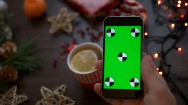 Pohled shora muž ruku hospodářství chytrý telefon s zeleným plátnem. Vánoční podrobnosti o pozadí stolu. Chromatický klíč. Sledování pohybu