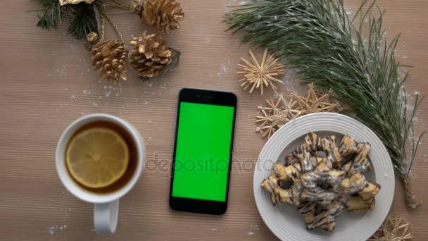 Pohled shora muž ručně pomocí chytrého telefonu s zeleným plátnem. Prstem, klepnutí a posouvání stránky na dotykovém displeji. Vánoční podrobnosti o dřevěný stůl pozadí. Chroma klíč