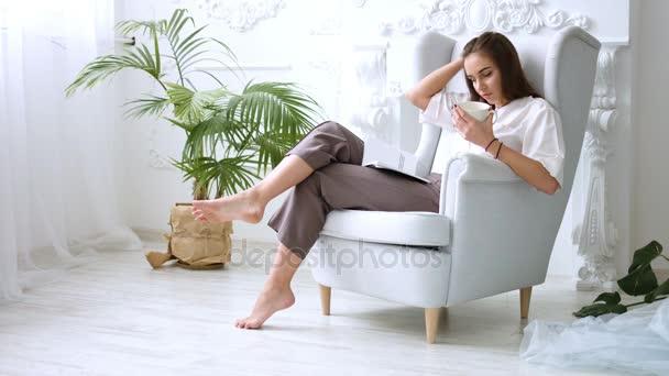 Csinos lány ivás, kávé vagy tea, és pihentető szék, egy könyvet olvas
