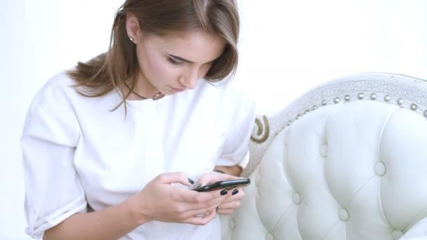 Attraktive Frau mit Handy. Junge schöne Mädchen SMS auf dem Handy auf dem Sofa sitzen. Frau mit app auf dem smartphone