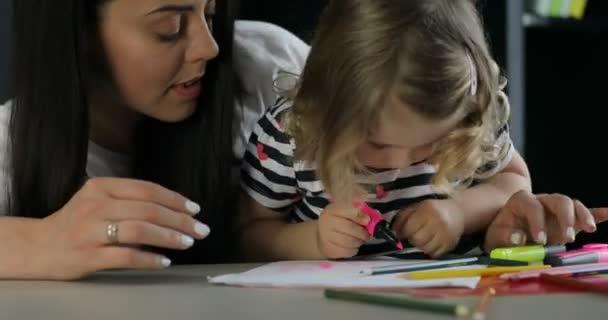 Szép kislány, szőke göndör haj, és az anyja elhelyezés-ra-a iskolapad. Lány rózsaszín Filc toll rajz egy papírlapra. Fedett. Közelről