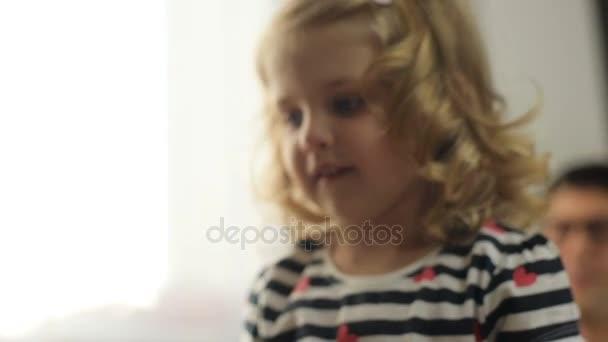 Portrét krásné děvčátko s kudrnatými blond vlasy a modré oči v domě chytat rukama bublina dmychadlo. Vnitřní.