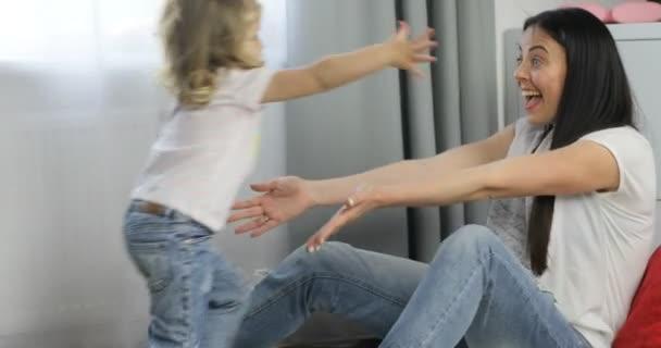 Kavkazské mladá žena sedící na podlaze v domácnosti a objímá ji málo dauther s blond kudrnaté vlasy. Vnitřní.