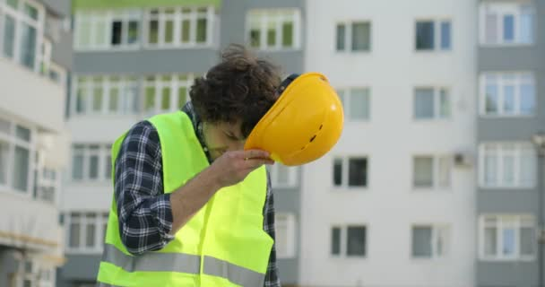 Attractive caucasian builder in a green vest going on unfinished construction background putting on the yellow helmet, looking around. Outdoor.