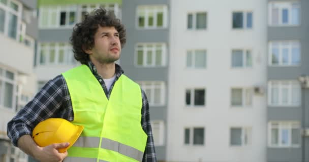 Young caucasian builder in a green vest standing on unfinished construction background putting on the yellow helmet, looking in side. Outdoor.
