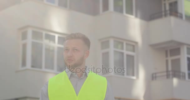 Portrait of beautiful builder with beard putting on yellow helmet on building background. Engineer at a construction site looking drawing. Outdoor.