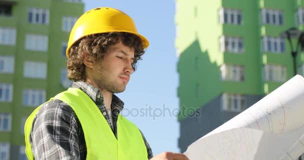 Boční pohled mladého architekta ve žluté helmě stojí na budování pozadí. Kavkazská inženýr na staveništi pohledu výkresu. Venkovní