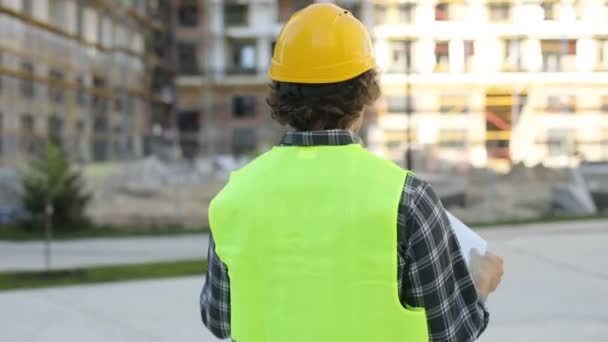 Back and side view of caucasian builder in yellow helmet and green vest looking drawing standing on unfinished construction background. Outdoor.