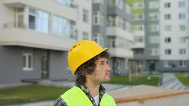 Portrait of caucasian builder in yellow helmet and green vest looking drawing standing on unfinished construction background. Outdoor.