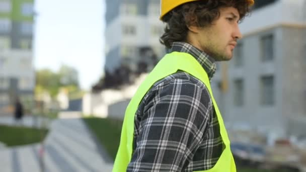 Side view of serious caucasian builder in yellow helmet and green vest on unfinished construction background. Close up.