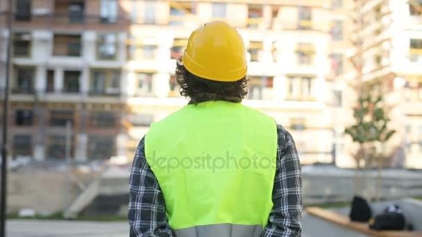 Zadní pohled na tvůrce v žlutou helmu a zelená vesta děje nedokončené stavby území, rozhlížel se kolem. Venkovní