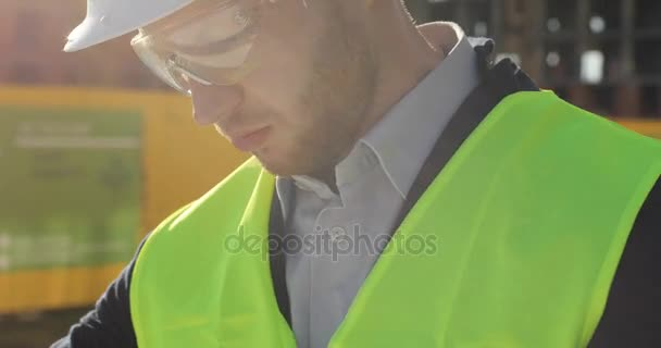Portrait of side view of serious caucasian builder in glasses and green vest looking drawing. Outdoor.