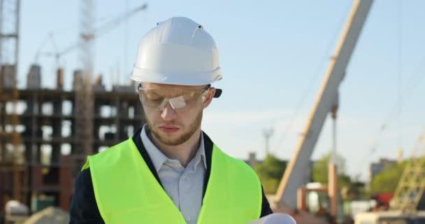 Mladý architekt v bílou helmu na pozadí rozestavěná stavba. Kavkazská tvůrce analýzy výkresu. Venkovní.