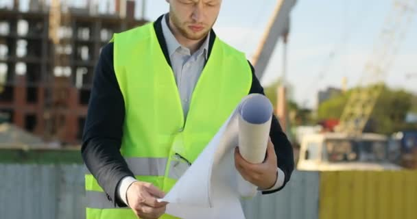 Attractive caucasian builder in white helmet on unfinished construction background. Serious builder analysing drawing and looking on the camera. Outdoor.