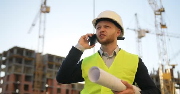 Kavkazská tvůrce v bílou helmu a žlutá vesta kreslení a mluví na mobilním telefonu na nedokončené konstrukce na pozadí