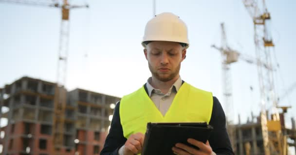 Stavební inženýr v bílou helmu a zelená vesta na staveništi pomocí tablet pro práci. Venkovní.