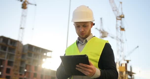 Serious builder in white helmet and green vest using the tablet for work on unfinished construction background.