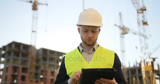 Concentrated young builder in white helmet and green vest at the construction site using the tablet for work. Outdoor.