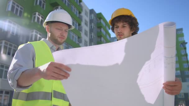 Two caucasian builders in protective helmets and green vest talking about conformity of construction process the drawing. Outdoor.