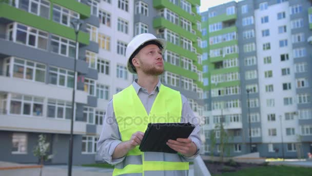 Builder engineer with white protected helmet and safety vest on construction site using tablet for tapping something. Outdoor.